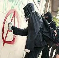 Dumbass in gas mask spraypainting anarchy sign on wall